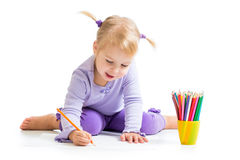 Kid girl drawing with colourful pencils Royalty Free Stock Images