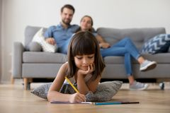 Kid girl drawing on floor with family in living room. Cute kid girl playing on warm floor at home, preschool little girl drawing with colored pencils on paper stock photos