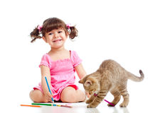 Kid girl drawing and playing with cat. Cute kid drawing with pencils. Kitten next to girl stock images
