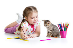 Kid girl drawing and playing with kitten. Kid girl drawing with pencils royalty free stock image