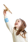 Kid girl dressed pilot helmet and playing with wooden airplane Royalty Free Stock Photos