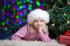Kid girl dressed in Santa hat near x-mas tree Royalty Free Stock Image