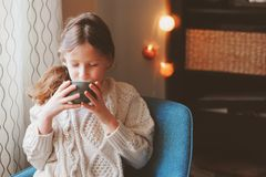 Kid girl drinking hot cocoa at home in winter weekend, sitting on cozy chair. In warm sweater royalty free stock photography