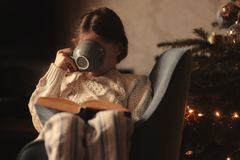 Kid girl drinking hot cocoa at home in winter weekend, sitting on cozy chair stock image