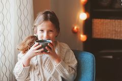 Kid girl drinking hot cocoa at home in winter weekend, sitting on cozy chair. In warm sweater stock photos