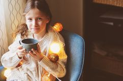 Kid girl drinking hot cocoa at home in winter weekend, sitting on cozy chair. In warm sweater stock image