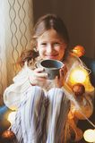 Kid girl drinking hot cocoa at home in winter weekend, sitting on cozy chair stock photo