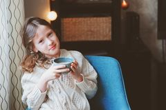 Kid girl drinking hot cocoa at home in winter weekend, sitting on cozy chair royalty free stock images