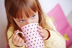 Kid girl drinking milk Stock Photos