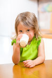 Kid girl drinking milk in kitchen. Kid girl drinking yogurt or milk in kitchen royalty free stock photography
