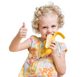 Kid girl eating banana and showing ok sign Stock Photography