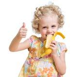 Kid girl eating banana and showing ok sign Stock Photography