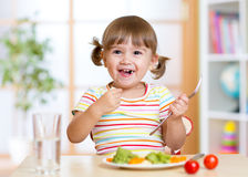 Kid girl eating healthy vegetables Stock Photography
