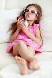 Kid girl eating on a sofa royalty free stock photo