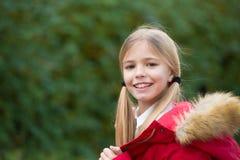 Kid girl enjoy fresh autumnal air. Child blonde long hair warm jacket nature background. Girl charming smile coat enjoy. Fall park. Child wear fashionable coat stock images