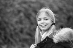 Kid girl enjoy fresh autumnal air. Child blonde long hair warm jacket nature background. Girl charming smile coat enjoy. Fall park. Child wear fashionable coat royalty free stock photo