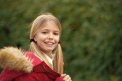 Kid girl enjoy fresh autumnal air. Child blonde long hair warm jacket nature background. Girl charming smile coat enjoy. Fall park. Child wear fashionable coat royalty free stock photography