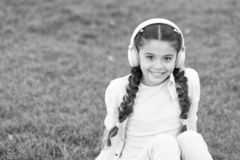 Kid girl enjoy music while sit on green grass meadow. Pleasant leisure time. Child headphones listen music. Fashion. Pretty cool girl in headphones listening stock photo