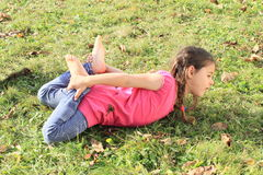 Kid - girl exercising stretching. Barefoot kid - girl with brown plaits in blue pants and pink t-shirt exercising stretching and yoga stock photos