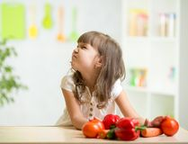Kid girl with expression of disgust against. Child girl with expression of disgust against vegetables Stock Photography