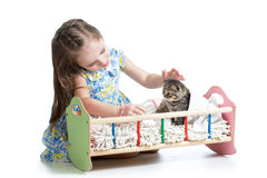 Kid girl feeding and playing kitten cat Stock Photos