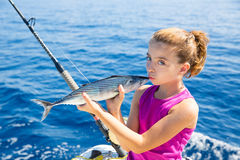 Kid girl fishing tuna bonito sarda kissing fish for release Royalty Free Stock Images