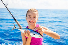 Kid girl fishing tuna little tunny happy with fish catch Stock Images