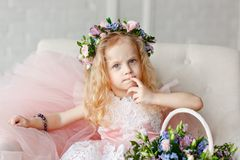 Kid - girl in a flower crown. Beautiful little girl in a bright studio sits, and looks into the camera near basket of royalty free stock photo