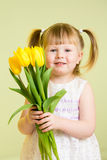Kid girl with flower gift on green Stock Photo