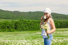 Kid girl with  flowers and glass of milk Stock Image