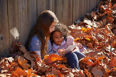 Kid girl friends playing tablet pc in autumn leaves Royalty Free Stock Photo