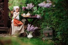 Kid girl at garden tea party in spring day with bouquet of lilacs syringa Stock Images