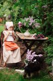 Kid girl at garden tea party in spring day with bouquet of lilacs syringa. Rustic wooden table and vintage dress Stock Image