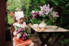 Kid girl at garden tea party in spring day with bouquet of lilacs syringa Stock Photo