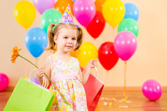 Kid girl with gifts and flower on birthday party Royalty Free Stock Photo