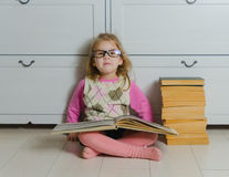 Kid girl in glasses with a book sitting on the floor reading Royalty Free Stock Images