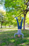 Kid girl handstands upside down in the park. In Valencia river royalty free stock images