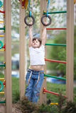 Kid girl hanging on the rings on kid playground. Kid girl hanging on the rings on a street playground, spring Stock Images
