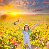 Kid girl in happy autumn vineyard field open arms red grapes bun Royalty Free Stock Image