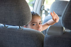 Kid girl happy greeting gesture hand in car indoor Royalty Free Stock Photography