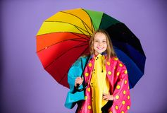 Kid girl happy hold colorful umbrella wear waterproof cloak. Enjoy rainy weather with proper garments. Waterproof. Accessories for children. Waterproof royalty free stock photography