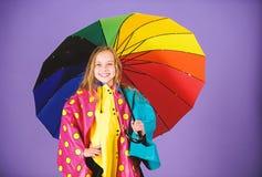 Kid girl happy hold colorful umbrella wear waterproof cloak. Enjoy rainy weather with proper garments. Waterproof. Accessories for children. Waterproof stock image