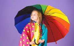 Kid girl happy hold colorful umbrella wear waterproof cloak. Waterproof accessories for children. Enjoy rainy weather. With proper garments. Waterproof royalty free stock photos