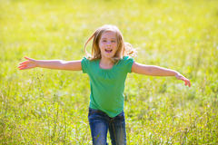 Kid girl happy running open hands in green outdoor Stock Photos