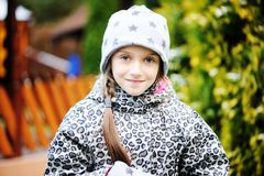Kid girl has fun in garden with first snow Royalty Free Stock Photography