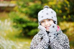 Kid girl has fun in garden with first snow Royalty Free Stock Photos