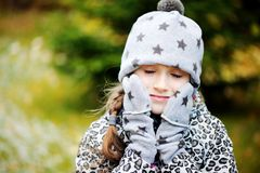 Kid girl has fun in garden with first snow Royalty Free Stock Photo
