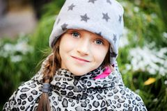 Kid girl has fun in garden with first snow Stock Photo