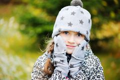 Kid girl has fun in garden with first snow Royalty Free Stock Image