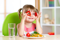 Kid girl having fun with food vegetables in Stock Photo
